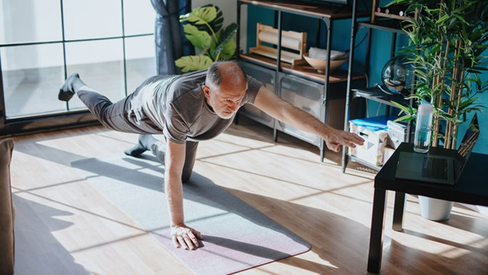 A man balances on one hand and knee on a yoga mat in his home. It seems as though he knows the importance of exercise for older people.