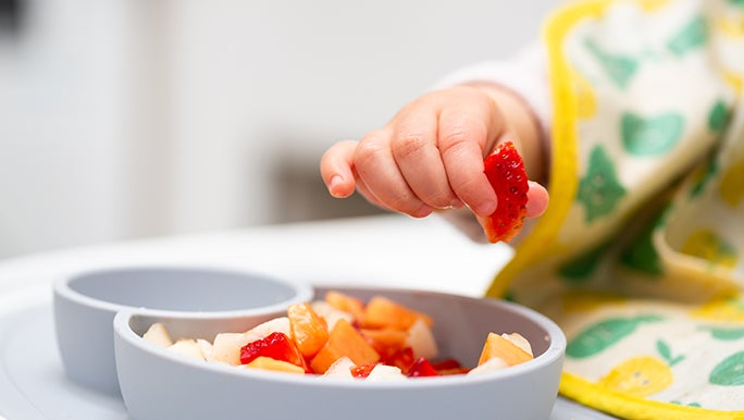 Up close, a baby is holding a strawberry in between their thumb and forefinger. There is a bowl of chopped fruit in front of them.