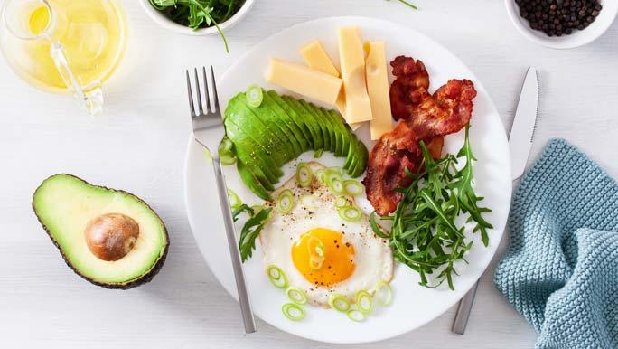 A healthy keto breakfast of avocado, cheese, eggs and bacon