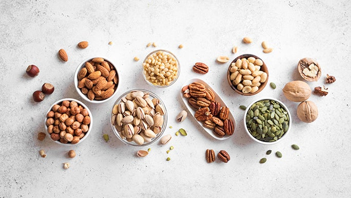 Various nuts are in bowls laid out on a white background.