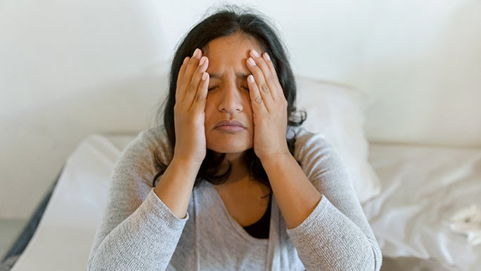 Woman sitting on a bed holds her face in her hands, she is experiencing menopause and sleep issues.