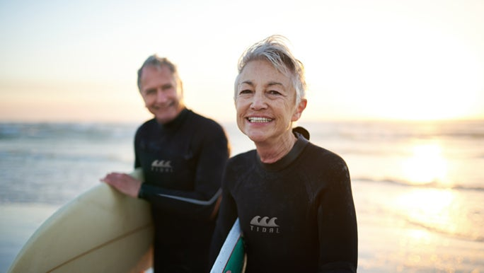 A healthy, ageing couple are standing on the beach at sunset. They are holding surf boards and wearing wetsuits.