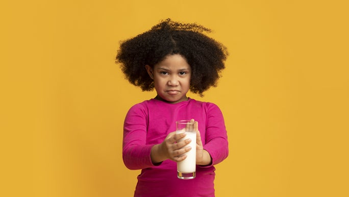 A young girl is holding onto a glass of milk, she seems frustrated to know that her farts smell really bad, from the constant milk she's been having.