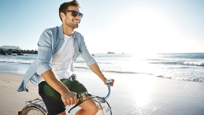 Smiling man enjoying the sun riding a bike at the beach