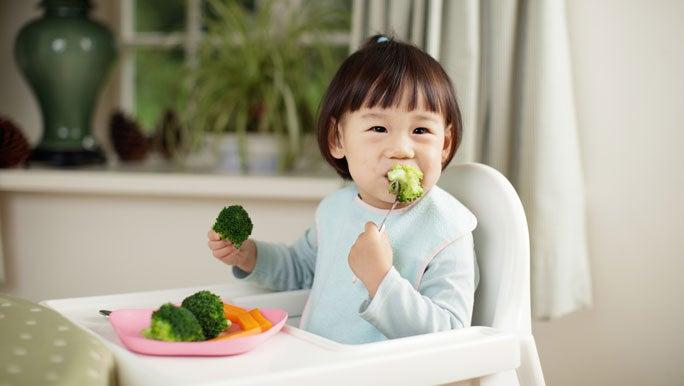 Toddler girl eating her vegetables