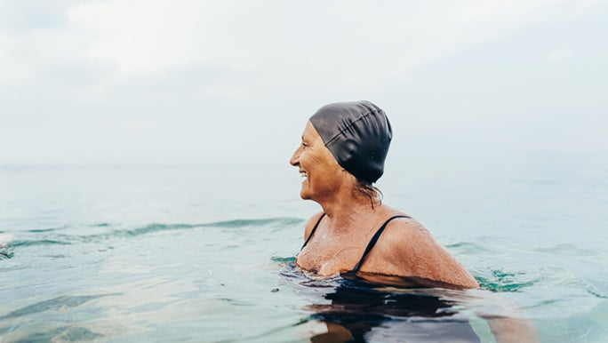 Lady wearing black swimmers and swimming cap enjoying the ocean. She is developing the healthy habit of daily exercise.