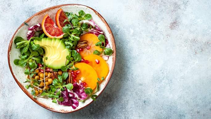 Vegan, detox Buddha bowl with turmeric roasted chickpeas, greens, avocado, persimmon, blood orange, nuts and pomegranate