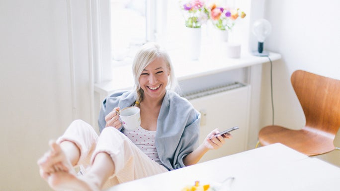 Young woman using a mobile phone while having healthy breakfast