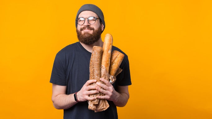 Smiling bearded man holding a bag of bread in front of an orange background