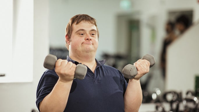 A man lifts small dumbbells in a gym setting, gym goals for beginners can be small and achievable.