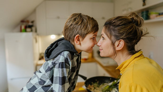 A mother and son are staring into each other's eyes. This is mindfulness, she is present in the moment.