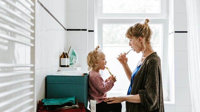 A woman and toddler are brushing their teeth together, mums know how to work smarter, not harder.