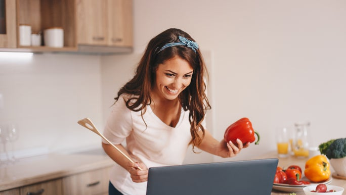 Woman in the kitchen following a recipe on her laptop