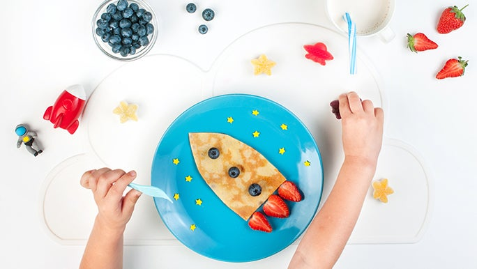 From above, a child's breakfast on a blue plate. It's a pancake shaped like a rocket ship with strawberries and blueberries on it. There is also a cup of milk with a straw and two arms of a child.
