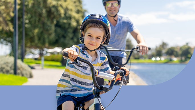 A young boy is riding bikes with his dad in the park