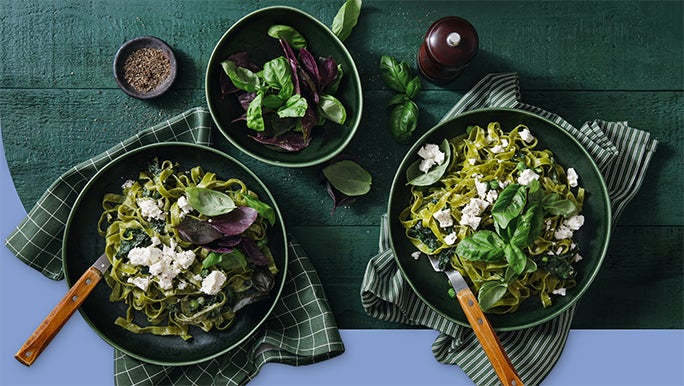 Two bowls of spinach and feta pasta with a green side salad