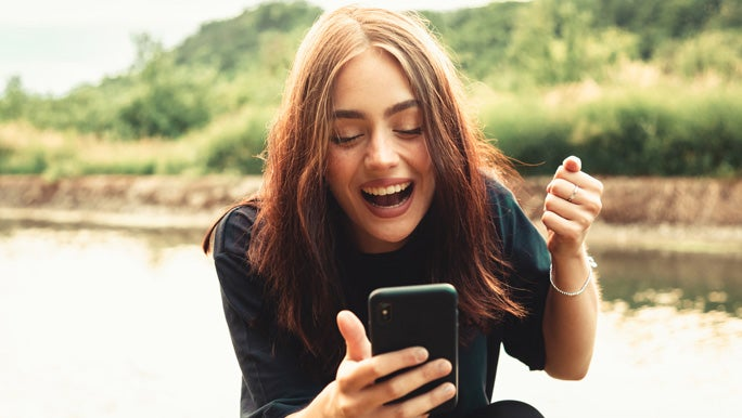 Happy bright smiling young woman sitting next to a river outdoors looking down to her phone face timing a friend