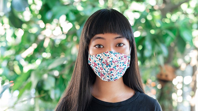 A woman looks straight on into the camera - she is wearing a mask and standing in front of a bunch of green plants.