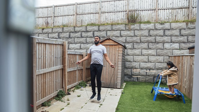 A bearded man skips in his backyard as a child jumps on a trampoline next to him. This is the perfect example of smart fitness goals in action.