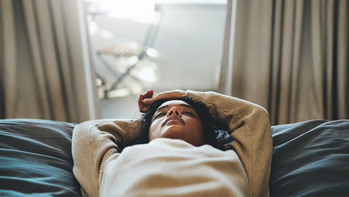 Lady lying in bed reflecting on the effects of alcohol on her health.