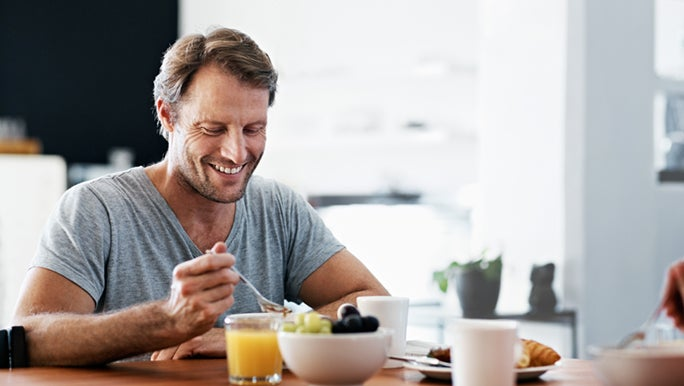 A man is eating a well balanced meal at his dining table. He is smiling because he knows eating well is how you can clear up adult acne.