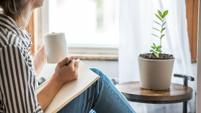 A woman writes in a notebook in a sunny corner of her home. She is wearing a striped shirt and drinking a cup of tea.