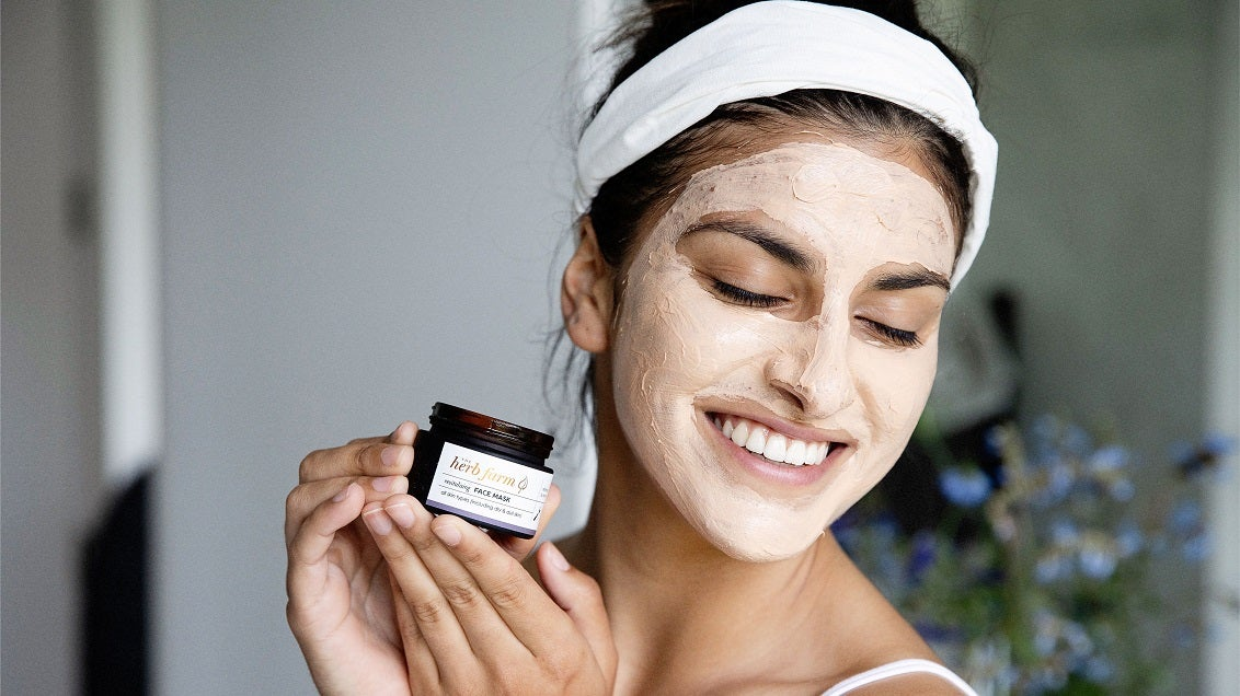 Young smiling woman using The Herb Farm Hydrating Face Mask