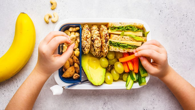 School healthy lunch box with sandwich, cookies, nuts, fruits and avocado