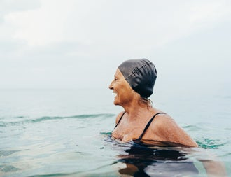 Mature woman in a black swimming cap and costume in the ocean
