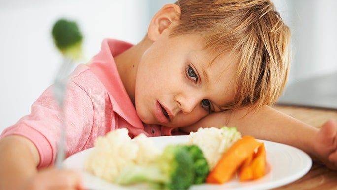 Little boy with his head on the table next to a plate full of vegetables. He is a picky eater who doesn't like vegetables.