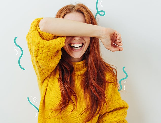 Young woman with long red hair in a yellow sweater covering her eyes with her arm and laughing
