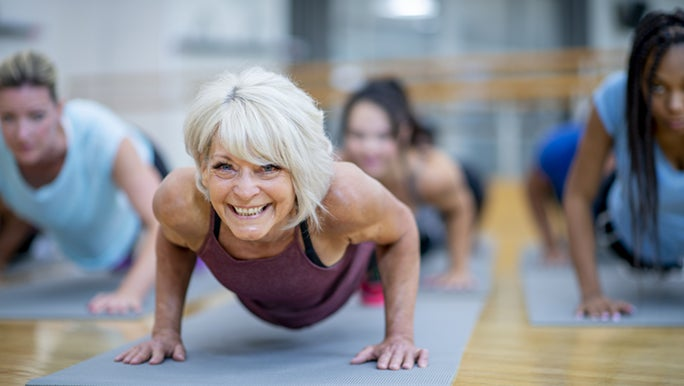 A woman is doing a plank pose on a Yoga mat in an exercise class. She looks very healthy for her age.