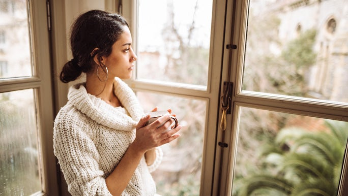 Young woman holding a mug of tea, gazing out the window