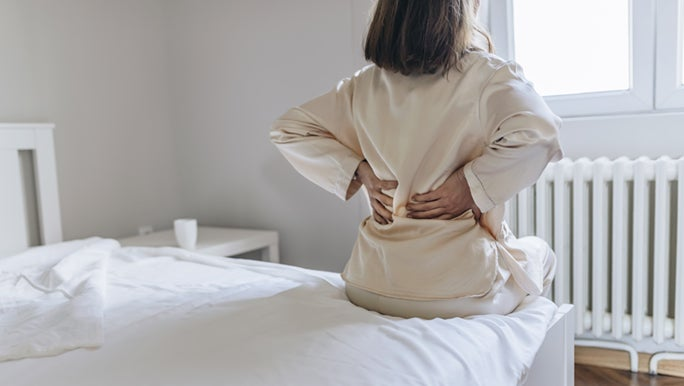 A woman in silk pyjamas is sitting on the side of a bed, holding her lower back because her muscles are sore.