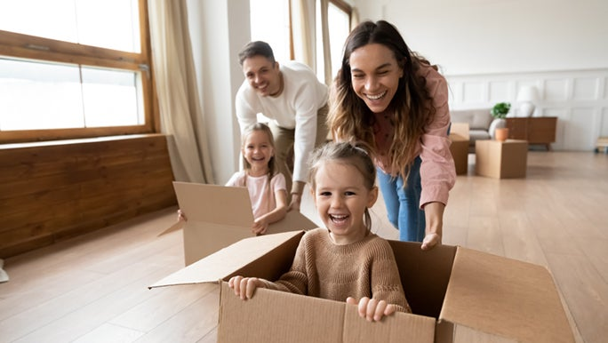 Two parents are pushing their kids around in empty cardboard boxes. Everyone looks happy.
