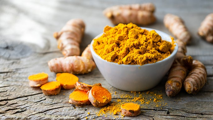A bowl of ground turmeric piled in a white bowl with whole pieces of raw turmeric on a wooden table.