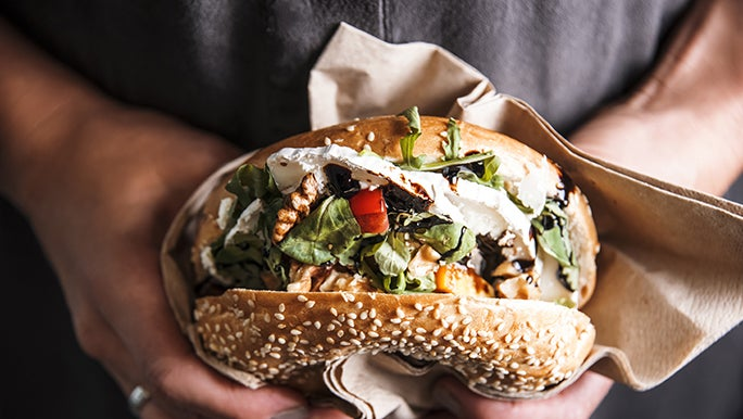A close up shot of two hands holding a burger or sandwich. it's full of veggies and protein.