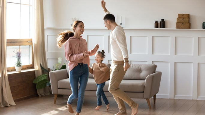 A family dances in their home happily, productivity hacks have changed their lives.