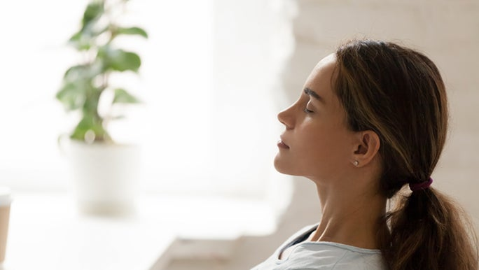 From the side, a woman is sitting with her eyes closed practising mindfulness for her nervous system, which can increase libido.