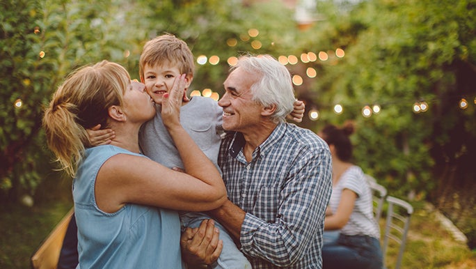 Two grandparents happily greet their grandchild at a post-lockdown backyard party.