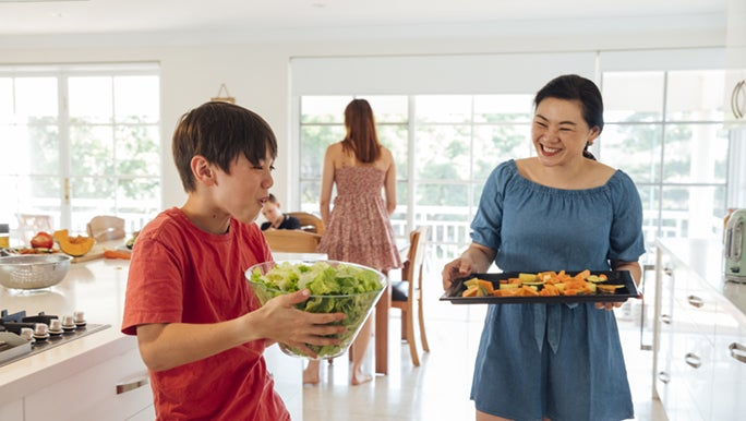 A mother and her son are in the kitchen standing as they prepare to walk to the dining table, his mother with a tray of healthy food in her hands. And her son, holding a bowl of salad.