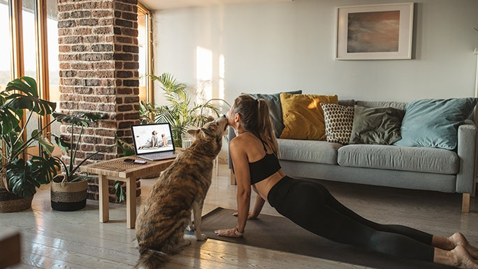 A woman practices Yoga in her lounge room with her dog. She is using self-care to combat brain fog.