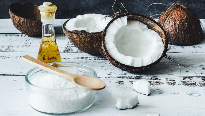 Coconut halves, desiccated coconut and coconut oil on a timber bench top