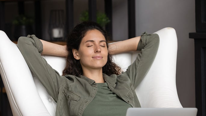 A lady is napping on a cozy chair, while she is in front of her laptop. This is one way to feel better after a bad day.