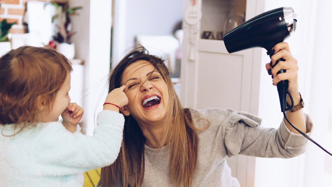 Woman is blow drying her hair and laughing as her toddler points to her eye, she has beautiful healthy hair.
