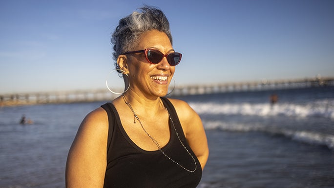 A woman is smiling at the beach, she wears a black singlet and red sunglasses.
