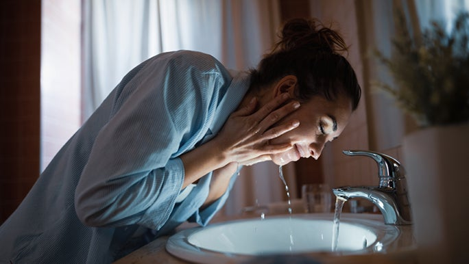 A lady is washing her face with both hands under the sink, as she's splashing water onto her face, so she can wash off the cleanser that she uses to care for her oily skin at night.