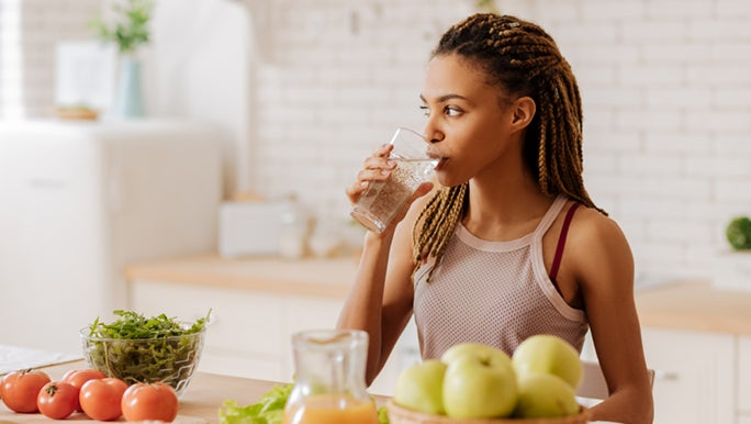 A lady is standing in front of her kitchen bench, drinking a tall glass of water, before she eats her breakfast. Perhaps more water and a healthy diet is one of the ways to look good without makeup.