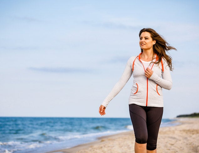 Woman with long brown hair walking along the beach in active wear