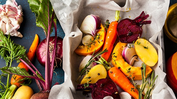 From above, a bunch of veggies are in a roasting pan and on the table next to it. Vegetables are some of the best foods for gut health.